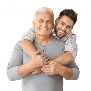 Young man and his father on color background